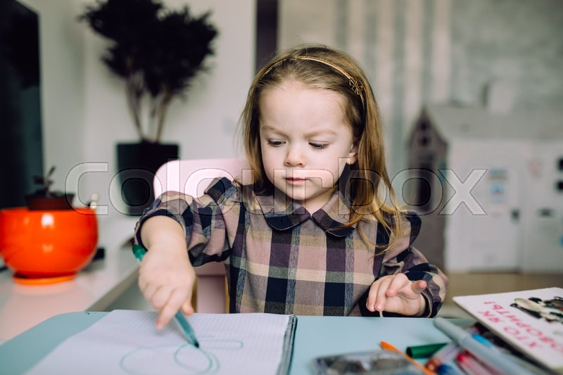 Happy little girl drawing with pencils at home, stock photo