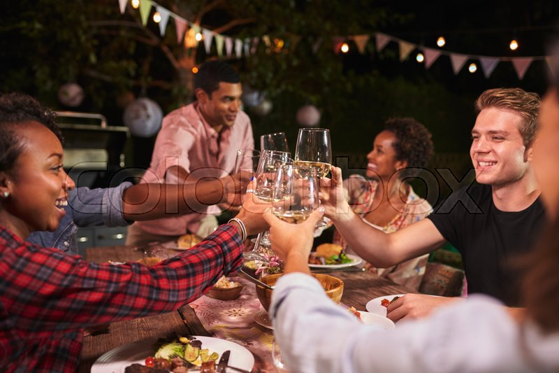 Friends and family toasting at garden dinner party, close up, stock photo