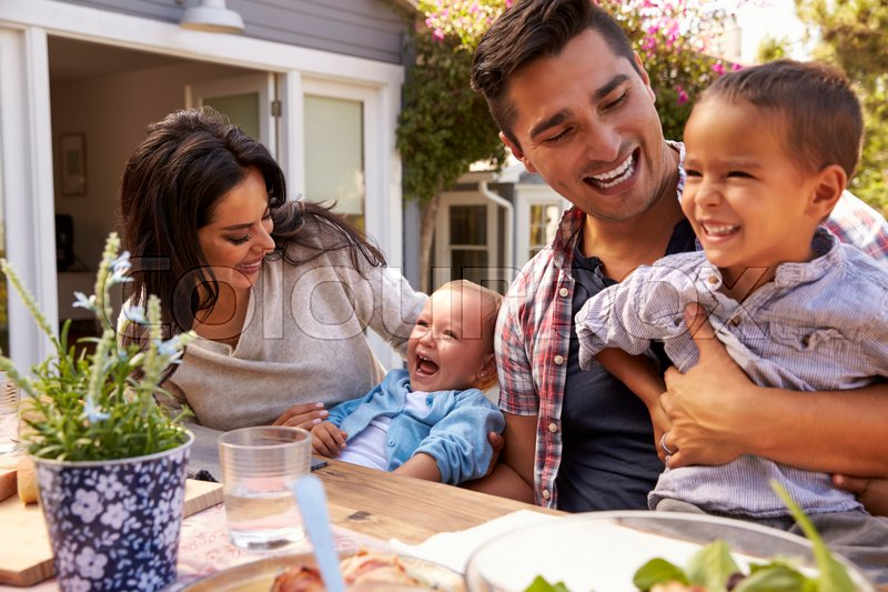 Family At Home Eating Outdoor Meal In Garden Together, stock photo