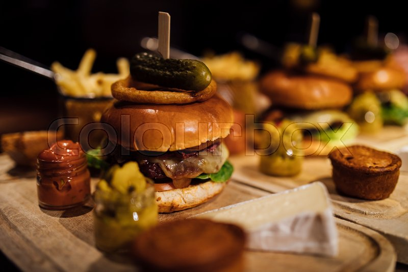 Close up shot of a restaurant burger meal with onion rings, bacon, pickle, chips and garnishes. , stock photo