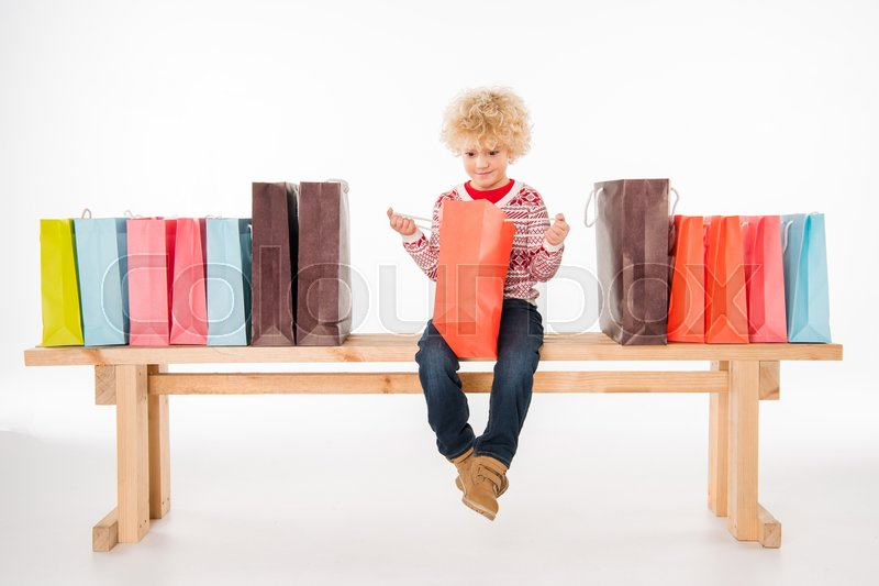 Kid sitting on bench with shopping bags and looking into one of them isolated on white, stock photo