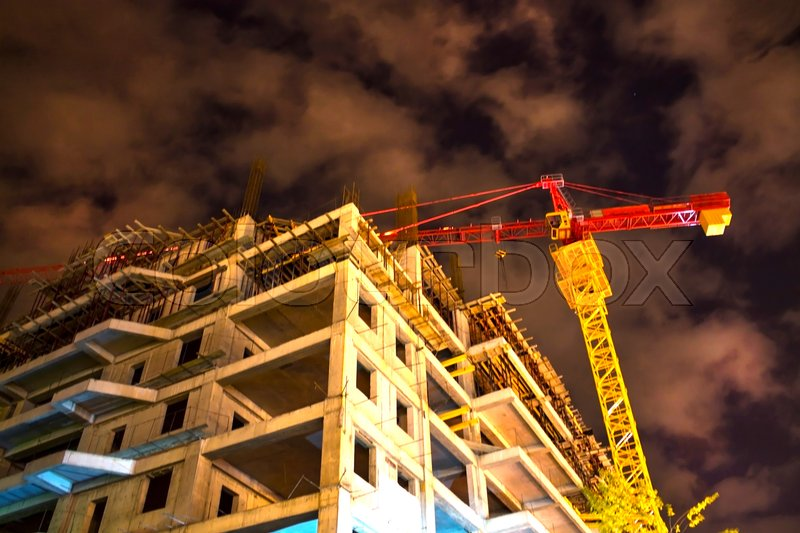 Unfinished building and hoisting crane at night time, stock photo