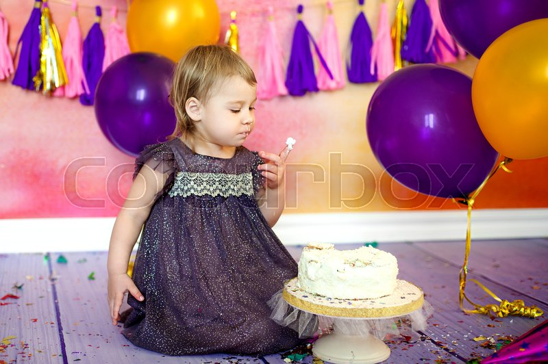 Two year old baby eating cake. Holiday birthday. Decor garlands and balloons, stock photo