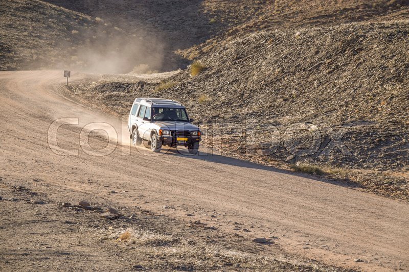 Desert road with driving off-road vehicle seen in Namibia, Africa, stock photo