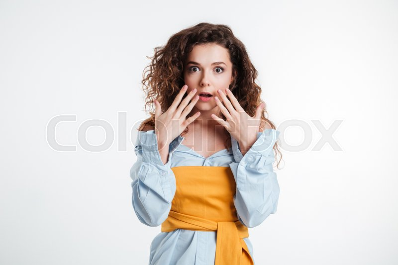 Stock image of 'Portrait of an astonished casual girl holding hands at her face isolated on a white background'
