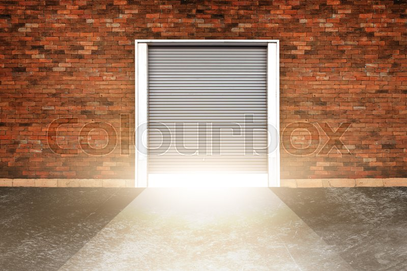 Opening roller shutter door and concrete floor outside factory building for industrial background and opening with old cement wall and light coming in. background of old vintage white brick, stock photo