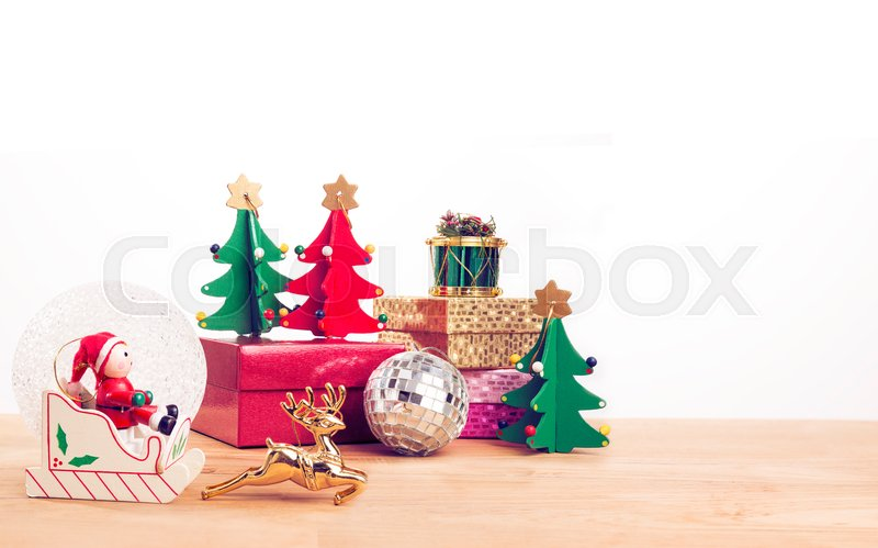 Santa Clause on sleigh and other Christmas theme ornaments on wooden table, in vintage retro color style, with white backgrtound and room for copy space, stock photo