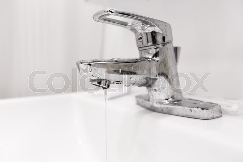 Bathroom water faucet with water leak running, stock photo