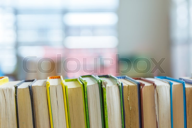 close up of hard covered library books line up on a shelf selective