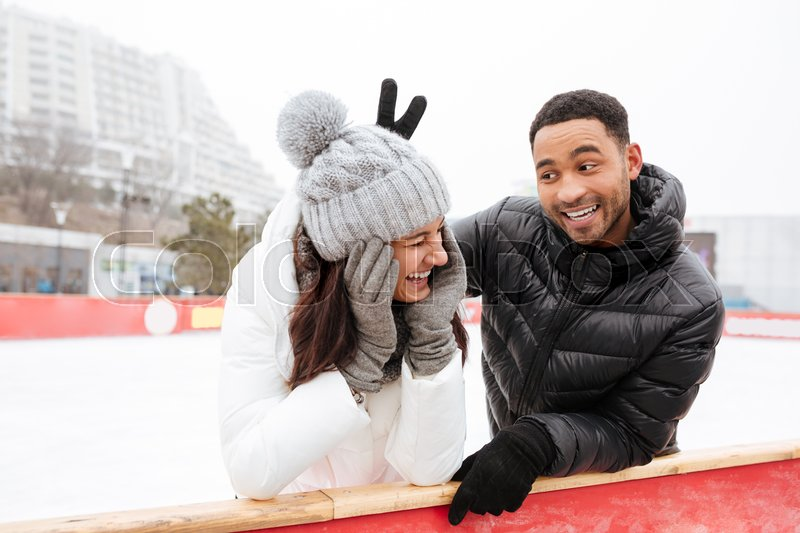 Photo of young happy funny loving couple skating at ice rink outdoors. Looking aside, stock photo