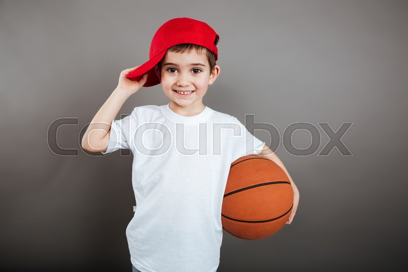 Portrait of cheerful little boy in red cap with basketball ball, stock photo