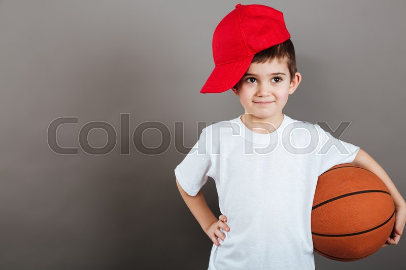 Cute little boy in red cap holding basketball ball over grey background, stock photo