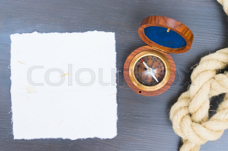 Old vintage compass with rope, copy space on white paper, stock photo