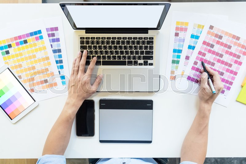 Top view of a young graphic designer working on a desktop computer and using some color swatches, top view, stock photo