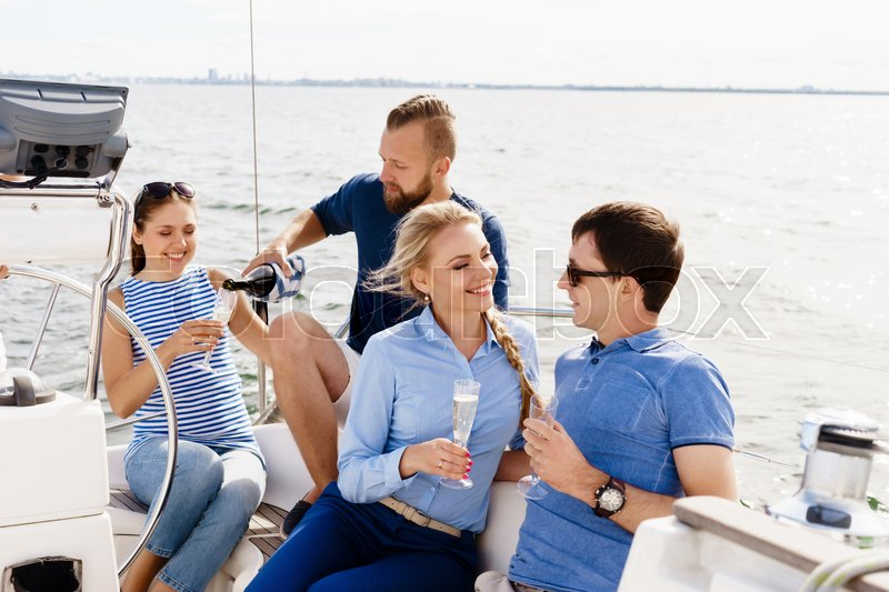 Group of happy friends having a party on a yacht and drinking champagne. Vacation, holiday, traveling, concept, stock photo