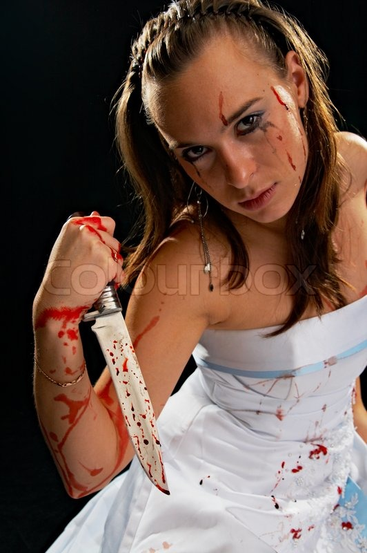 Portrait of the sad woman with knife with blood on black background, stock photo