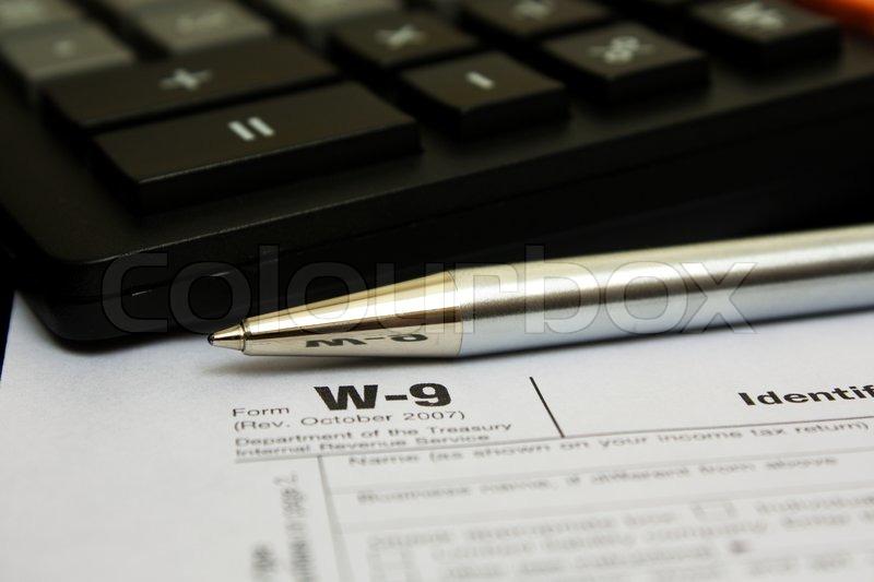 Pen og lommeregner på W -9 selvangivelsen | stock foto | Colourbox