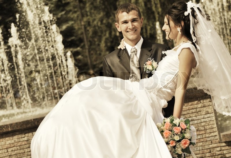 The groom holds the bride on hands a happy newly married for Trisha yearwood wedding dress