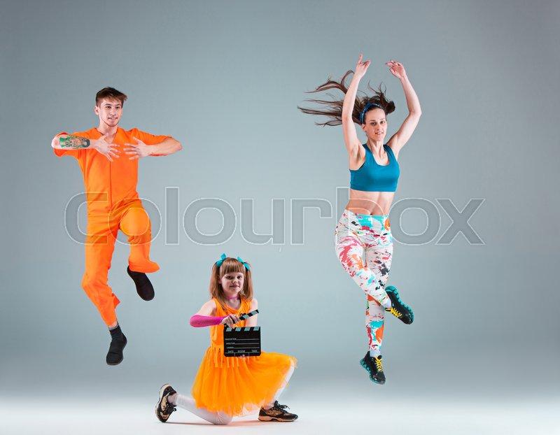 The man, woman jumping and dancing hip hop choreography and posing at studio on gray, stock photo
