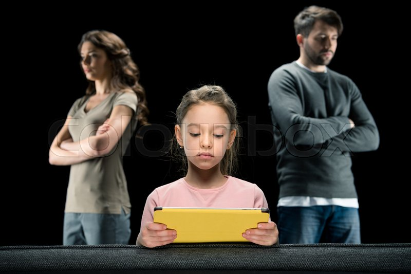 Girl using digital tablet while parents standing with crossed arms on black, family problems concept , stock photo