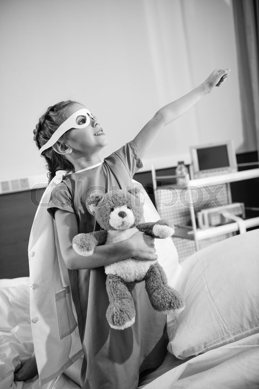 Black and white photo of little girl superhero playing with teddy bear i hospital, stock photo
