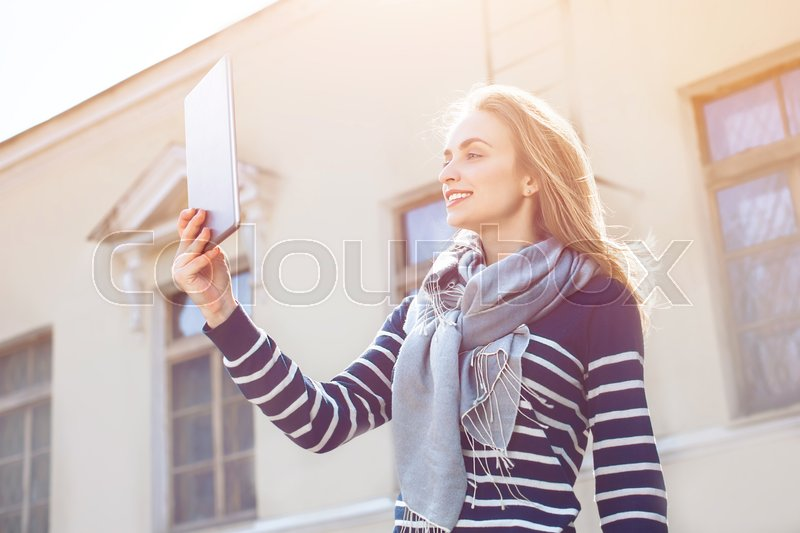 Young hipster girl with trendy look is shooting video on portable touch pad of a street view during her travel abroad. Charming woman is photographing herself with front camera of digital tablet, stock photo