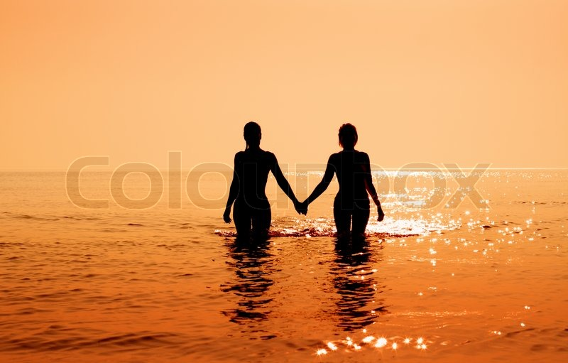 Stock image of 'Silhouette image of two bikini girls holding hands'