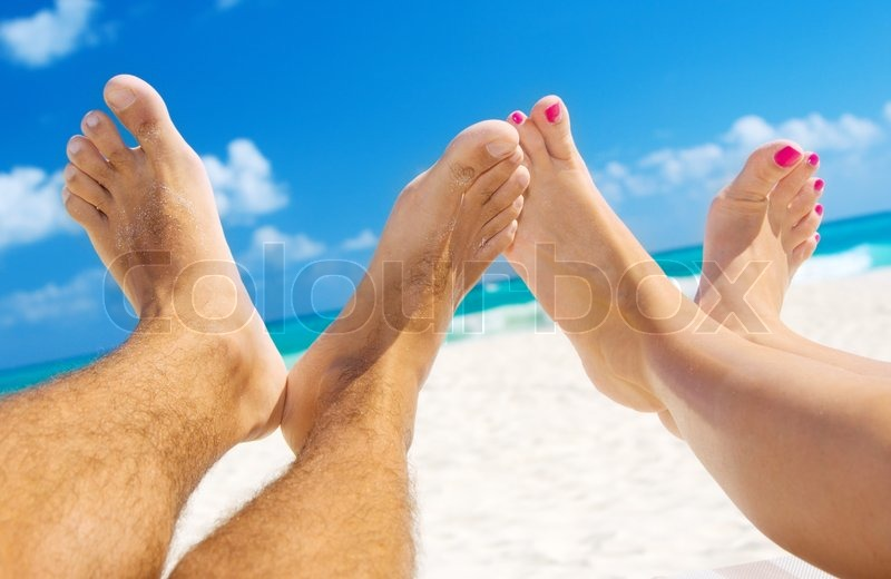 Stock image of 'Picture of male and female legs over tropical beach background'