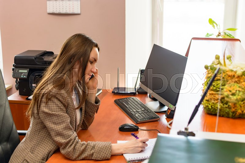 Girl Secretary works in the office, a lot of talking on the phone. hard work. unpleasant conversations, stock photo