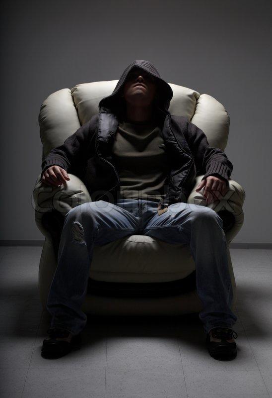 Dark Portrait Of Dangerous Man Sitting In White Chair