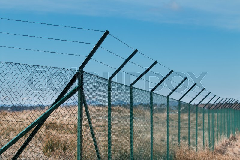 Tall fence with barb wire | Stock Photo | Colourbox