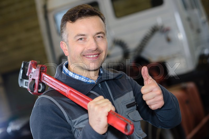Smiling mature plumber holding a wrench, stock photo