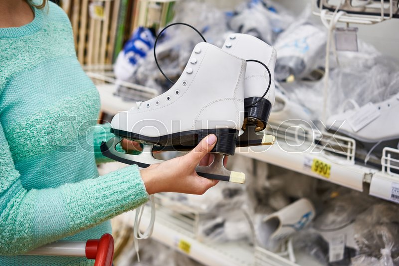 Woman chooses figure skates in the sports shop, stock photo