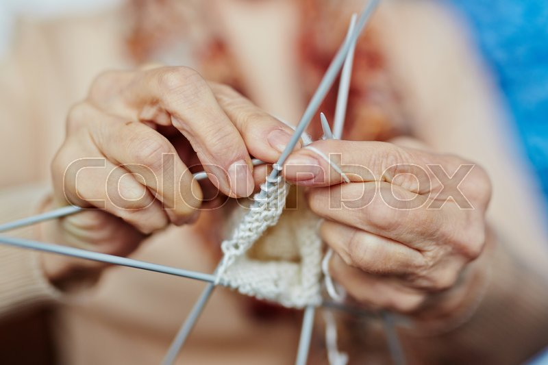 Senior woman knitting warm sweater for her son with white wool, close-up shot, stock photo