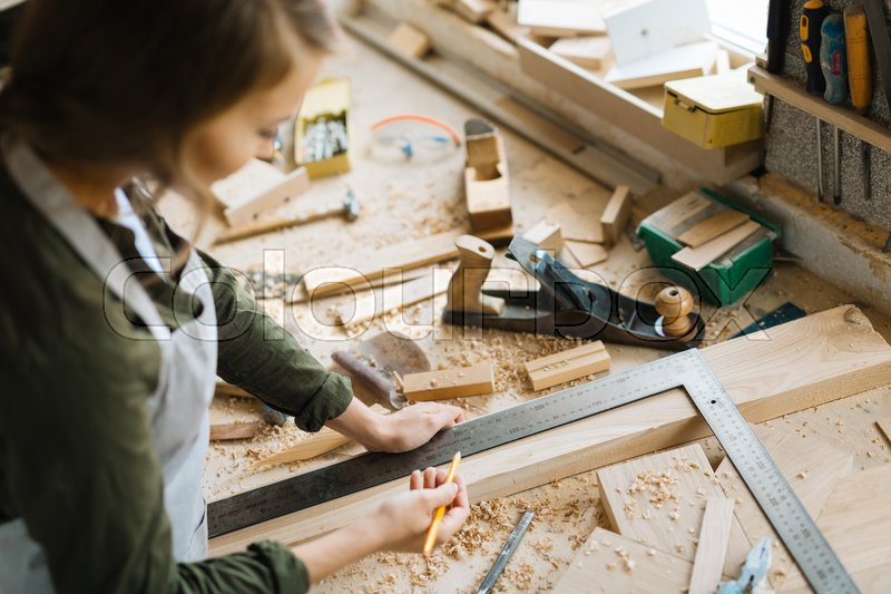 Profile view of confident young craftswoman marking measurement with help of steel framing square and pencil in workshop, stock photo