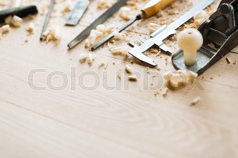 Still life of carpentry tools on wooden table background, shaving scattered everywhere, close-up shot, stock photo