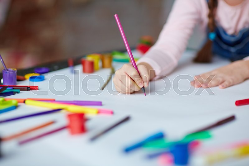 Little girl holding crayon or highlighter on paper, stock photo