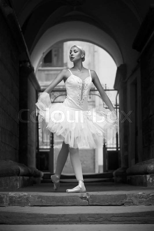 Dancing on the streets. Monochrome portrait of a beautiful ballerina standing in an archway , stock photo