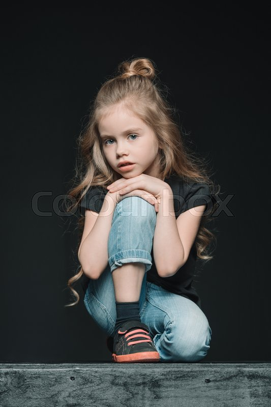 Pensive girl sitting and looking at camera, on black, stock photo