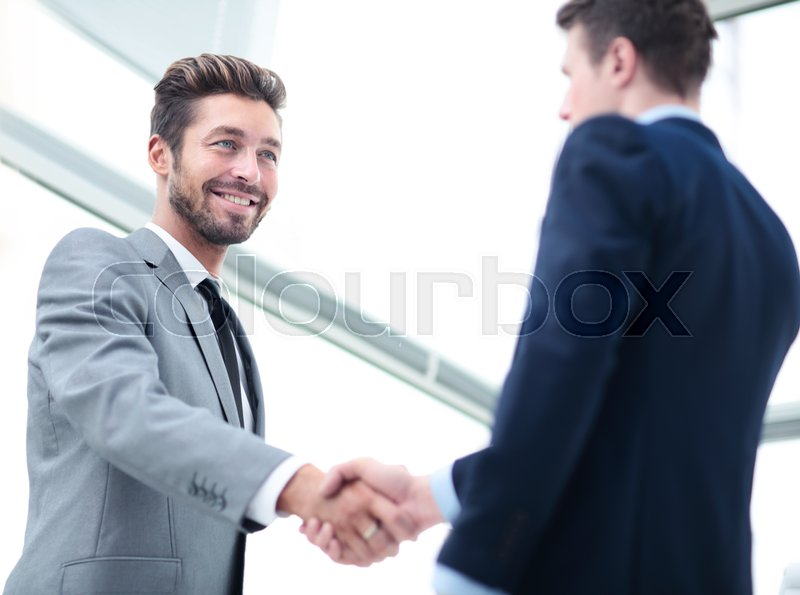 Two business people shaking hands and looking at each other with smile, stock photo