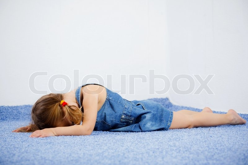 Stock image of crying child lying on the floor