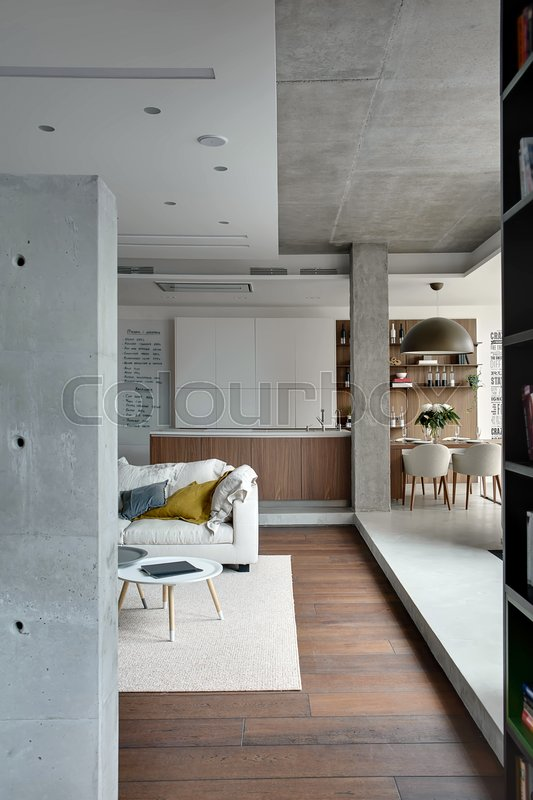 Interior In A Loft Style With Concrete Columns. There Is A Kitchen Island,  White Lockers, Shelves With Bottles And Books, Table With Dishes And  Chairs, ...