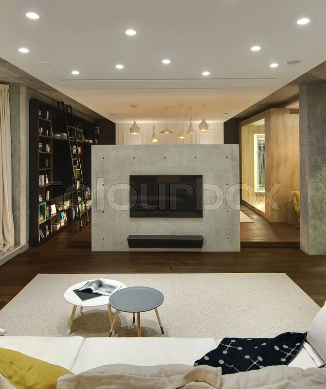 Studio Apartment In A Loft Style With Luminous Lamps There Is Sofa Pillows Small Round Tables Concrete Wall Tv Dark Bookcase Ladder
