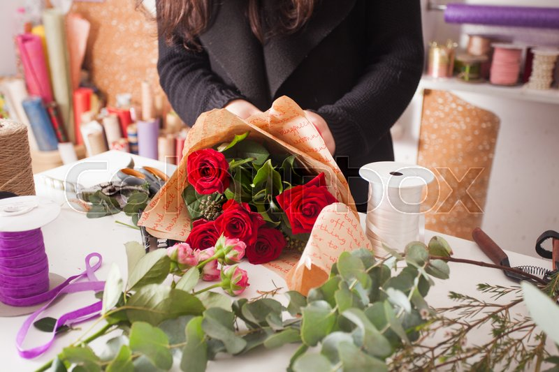 Florist making fashion bouquet of beautiful red roses, stock photo