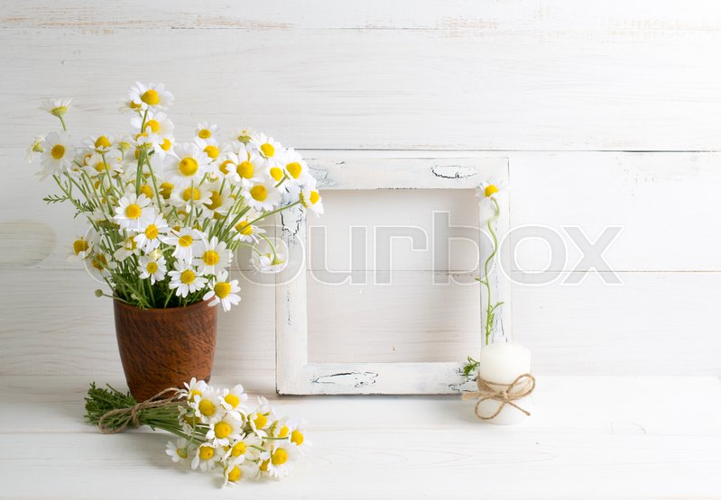 Daisy flowers bouquet with photo frame and candle on white wooden ...