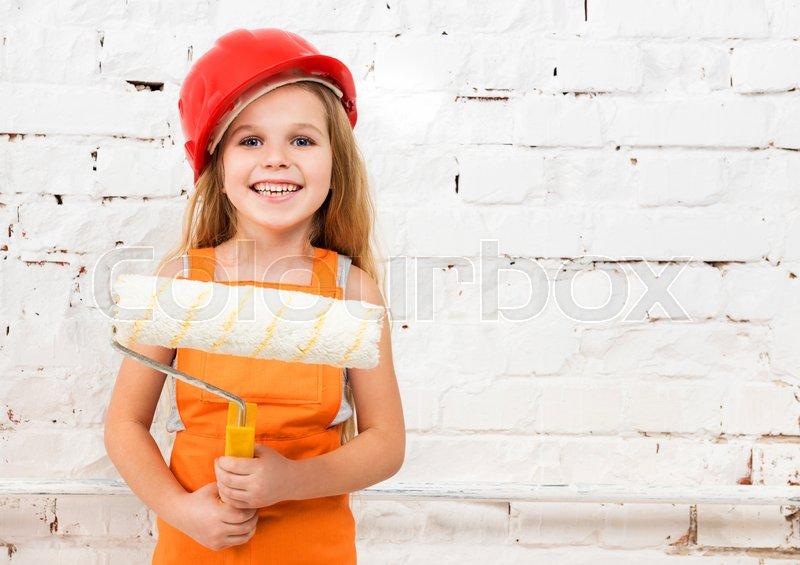 Little girl-worker in orange uniform with paint roller in hands, stock photo