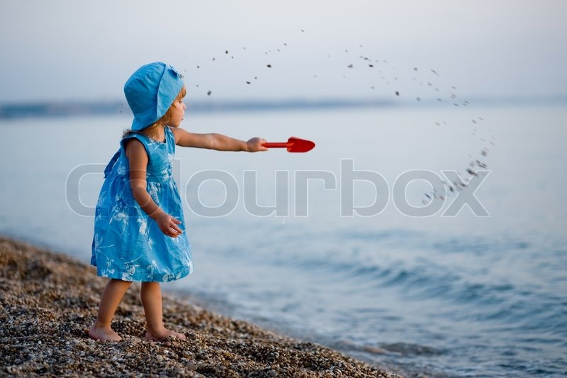 Stock image of 'Baby girl in blue dress and hat playing on beach at sunset alone'