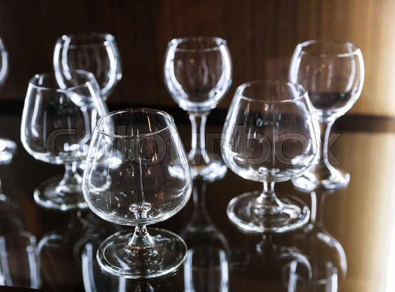Clean alcohol glasses on wooden shelf, selective focus.Interior decoration for kitchen, restaurant or bar, stock photo
