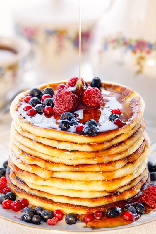 Pancakes with berries and honey, high key, stock photo