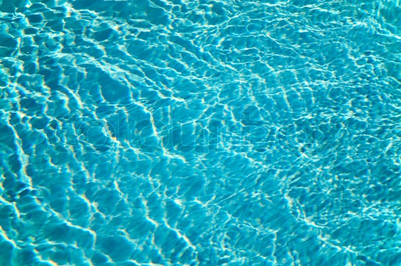Patterns of sunlight rippling o n a swimming pool water ...